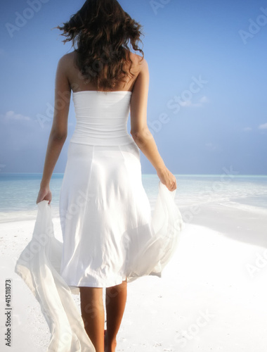 Girl walking on a white sandy beach on the Maldives (Malediven)