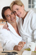 Couple dressed in bathing robes in the kitchen