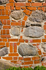 Big stones in red brick wall. Architecture closeup