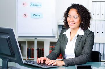 junge frau im büro schreibt am computer