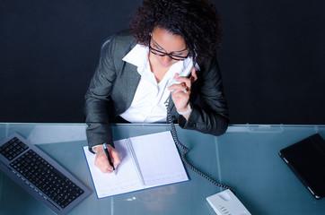 junge frau macht sich notizen beim telefonieren