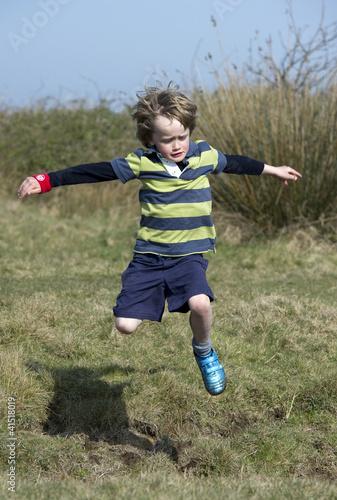 Boy jumping a ditch