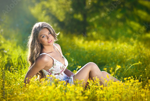 Happy and attractive teen girl in green and canola  field