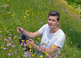 Sympathetic young business man in nature workstation on meadow poster