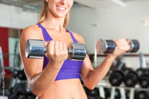Sport - Frau trainiert mit Hanteln im Fitnessstudio