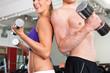 Sport - Paar trainiert mit Hanteln im Fitnessstudio