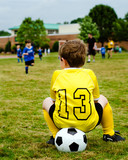 Boy in soccer uniform watching youth game