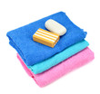 Stack of towels and soap isolated on white