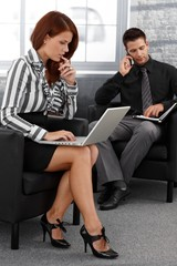 Businesspeople working in office lobby