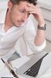 Gestresst im Büro - Mann hat Migräne