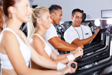 fitness people biking in gym with personal trainer