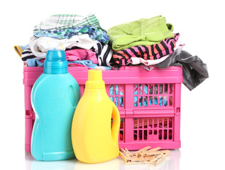 Clothes with detergent in pink plastic basket isolated on white