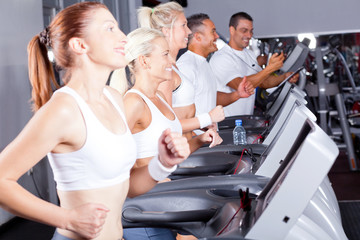 group of fitness people exercising with treadmill in gym