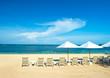 beach chairs and umbrellas on tropical beach