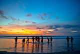 young people at sunset beach in Kuta, Bali