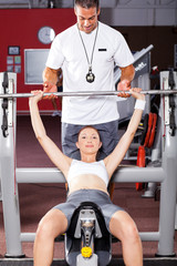 woman exercising with barbell with help of personal trainer