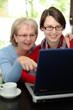 Mutter und Tochter in der Küche am Laptop