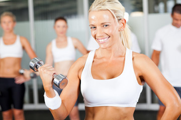young fitness woman doing dumbbell exercise in gym