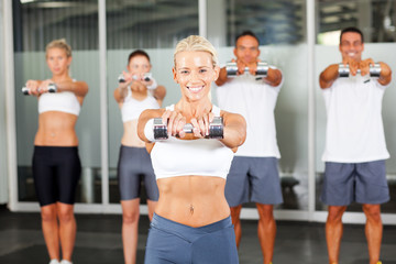 group of people doing aerobics with dumbbells in gym