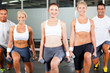 group of people exercise in gym with dumbbells