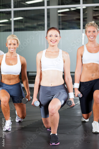 group of fitness woman using dumbbells in gym