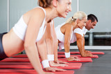 group of fitness people doing pushups in gym