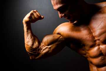 strong bodybuilder posing on black background
