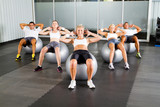 group of people doing workout with fitness balls in gym