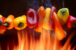 Red yellow and orange peppers over flames