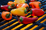 Red yellow orange peppers on a hot grill