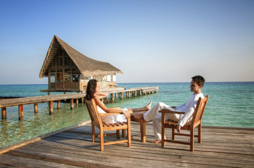 Happy love couple sitting on a jetty at the beach (maldives)