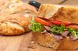 Freshroast beef picnic sandwich on wood board.