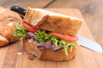 Fresh roast beef sandwich on wood cutting board.