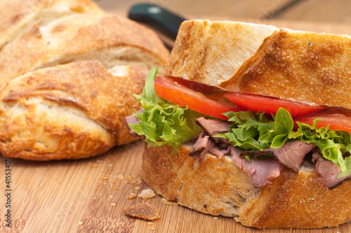 Freshroast beef picnic sandwich on wood board.