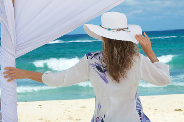 Woman under a gazebo looking at the sea.