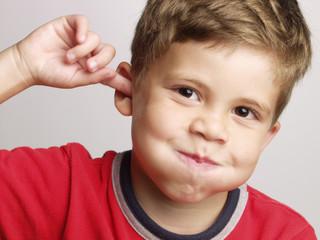 Retrato de un niño feliz y expresivo tocándose el oído.