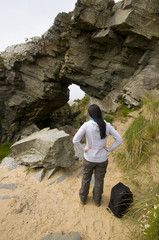 woman looking through arch made from rock