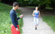 Personal trainer timing a female runner. Selective focus.