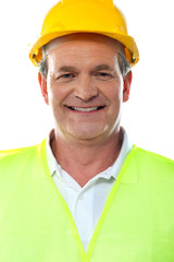 Smiling senior builder wearing hardhat