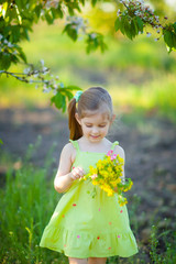 Adorable kid with bouquet of flowers in summer garden
