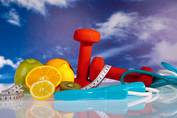 fitness dumbbells, jump rope and fruits