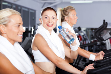 young woman drinking water in gym