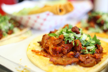 Al pastor soft tacos with taquitos at a local taqueria.