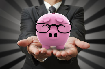 Businessman shows a piggy bank