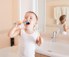 Boy cleaning teeth in bathroom