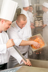 Two professional chefs cooking in kitchen