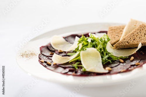 Vegetarian carpaccio with beetroot,nuts and toast