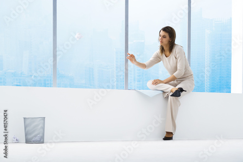 Woman throwing paper ball toward trash can