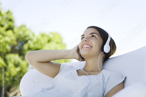 Teenage girl listening to headphones, looking up, smiling