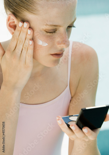 Woman applying sunscreen, looking into compact mirror